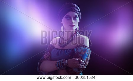 Portrait of a beautiful gypsy woman on a black background. National gypsy costume, ethnic. Make-up and headdress.