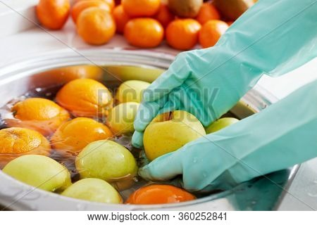 closeup of a man in the kitchen, wearing gloves, washing some fruits and vegetables freshly purchased, on the sink with water and food sanitizer