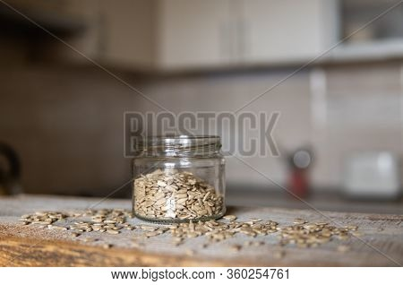 Sunflower Seeds In A Jar And Scattered Seed On The White Vintage Table With A Kitchen On Background.
