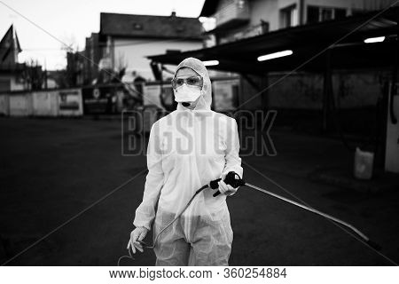 Sanitation Service Worker Spraying Disinfectant With A Spray Gun In Hazmat Suit,n95 Mask And Protect