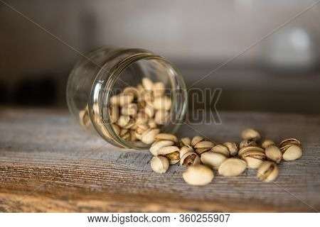 Pistachios Scattered On The White Vintage Table From A Jar. Pistachio Is A Healthy Vegetarian Protei