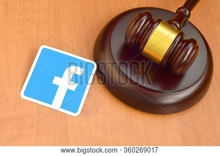 Facebook Paper Logo Lies With Wooden Judge Gavel. Entertainment Lawsuit Concept