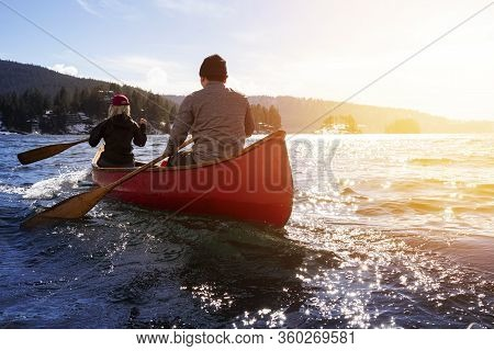 Couple Friends On A Wooden Canoe Are Paddling In Water During A Vibrant Sunny Day. Taken In Indian A