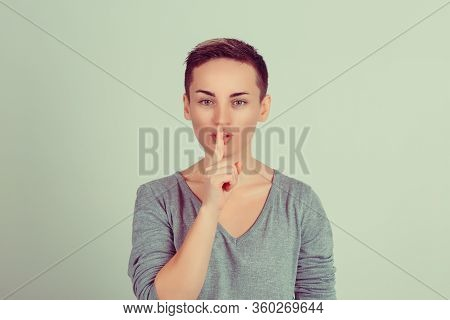 Shh. Woman Wide Eyed Asking For Silence Or Secrecy With Finger On Lips Hush Hand Gesture Green Backg