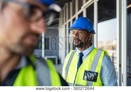 Engineer builder at construction site looking away and thinking. Mature african man architect wearing safety helmet, contemplating construction site. Thoughtful construction worker, vision concept.
