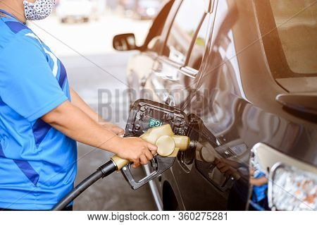Service Staff Holding A Pump Refuel A Cars At Gasoline Station. Service Staff Wear Mask Disease Prot