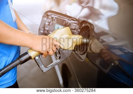 Close Up Hand Holding A Pump Refuel A Cars At Gasoline Station. Refueling Service. Gasoline Station.
