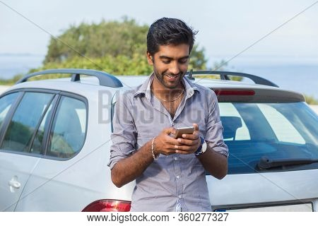 One Young Handsome Indian Man Smiling Holding Looking At Mobile Phone. Cheerful Asian Model Outdoors