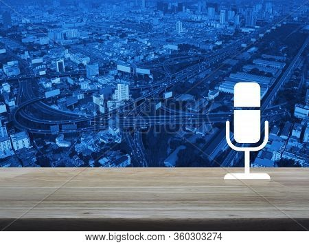 Microphone Flat Icon On Wooden Table Over Modern City Tower, Street, Expressway And Skyscraper, Busi