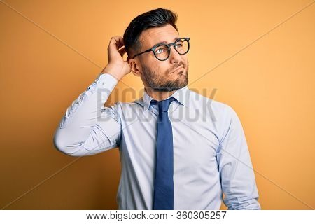 Young handsome businessman wearing tie and glasses standing over yellow background confuse and wondering about question. Uncertain with doubt, thinking with hand on head. Pensive concept.