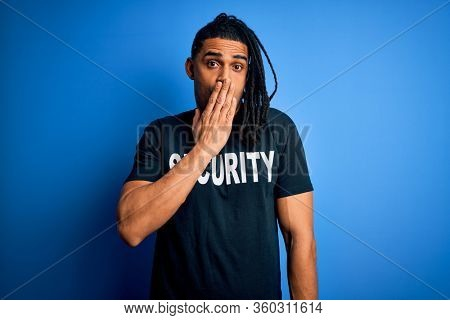 Young african american afro safeguard man with dreadlocks wearing security uniform cover mouth with hand shocked with shame for mistake, expression of fear, scared in silence, secret concept