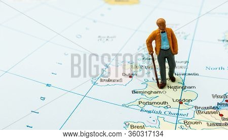 Old Man And Coronavirus Outbreak. Small Figurine And Map Of The United Kingdom. Coronavirus Pandemic
