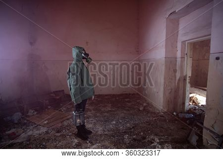 Post apocalyptic survivor in gas mask in a ruined building. Environmental disaster, armageddon concept.