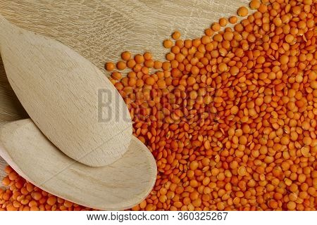 Flat Lay. Two Wooden Spoons And Scattered Orange Lentils On A Wooden Table. Background Texture Of Le