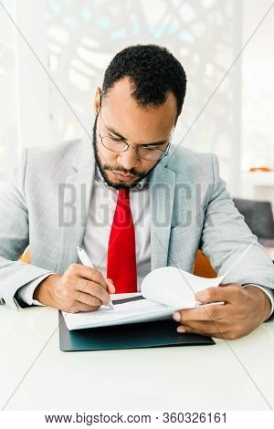 Serious Businessman Writing On Papers. Focused Young African American Businessman In Eyeglasses Sitt