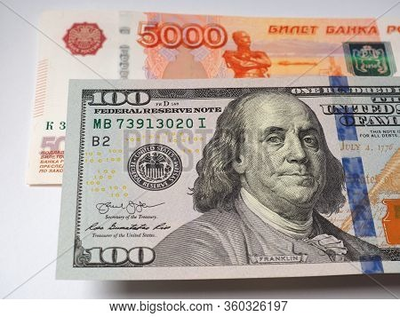 Bill 100 Us Dollars Hanging Over Banknote 5000 Russian Rubles. Close-up
