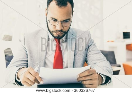 Serious Businessman Working With Papers. Focused Young African American Businessman In Eyeglasses Si