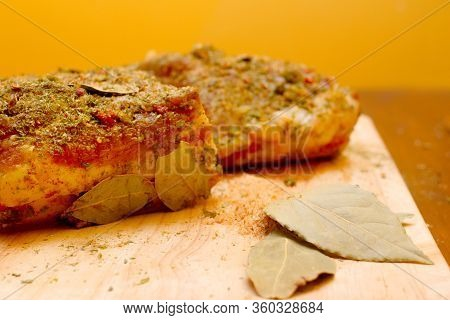Two Pieces Of Pork Bacon Preparation On A Blackboard And Yellow Background. Harvesting Bacon. Whole