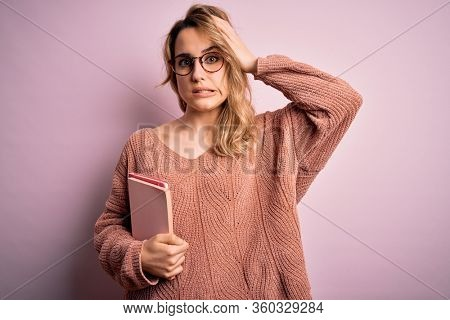 Young beautiful blonde woman wearing glasses holding notebook over pink background stressed with hand on head, shocked with shame and surprise face, angry and frustrated. Fear and upset for mistake.
