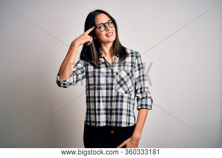 Young brunette woman with blue eyes wearing casual shirt and glasses over white background Smiling pointing to head with one finger, great idea or thought, good memory