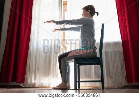 Beautiful Young Girl Doing Exercises At Home Using Chair.
