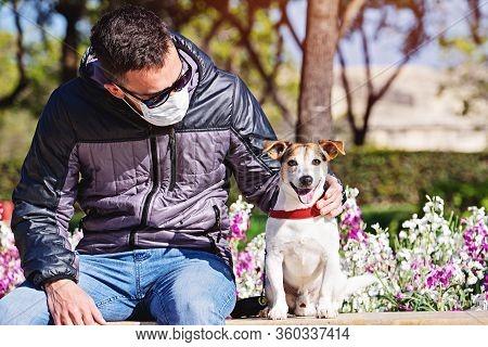 Man Wearing Face Mask Looking At Dog During Coronavirus. Short Walks During Covid-19 Pandemic. Avoid