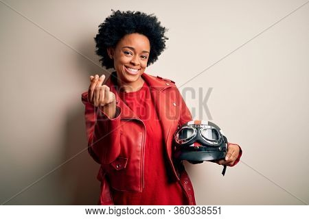 Young African American afro motorcyclist woman with curly hair holding motorcycle helmet doing money gesture with hands, asking for salary payment, millionaire business