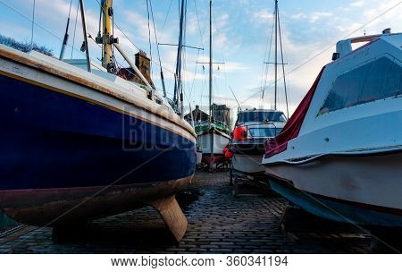 Sailing And Leasure Boats Stored On A Cobbled Pier For The Winter With An Historic Medieval Tower An
