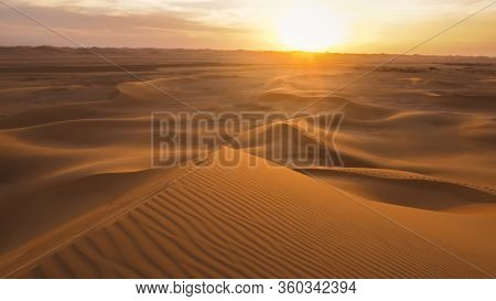 Amazing desert sunset. Beautiful Arabian desert with warm colors. Colorful contours of sand dunes at