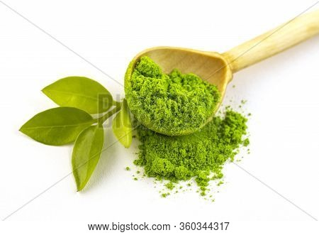 Dry Green Tea Powder Matcha Tea With A Wooden Spoon And Whole Leaves, Isolate On A White Background.