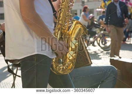 Sideview Of Street Artist Playing Saxophone In Front Of Live Audience.