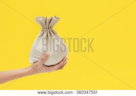 Hand Holds A Textile Bag On A Yellow Background, The Concept Of Money And Financial Assistance, Bank