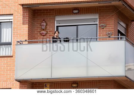 A woman talking on the  in balcony after Spain imposed a lockdown to slow down the spread of the coronavirus disease in Valencia, Spain on April 5, 2020.