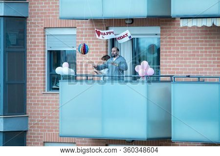 A couple celebrating a birthday in balcony after Spain imposed a lockdown to slow down the spread of the coronavirus disease in Valencia, Spain on April 6, 2020.