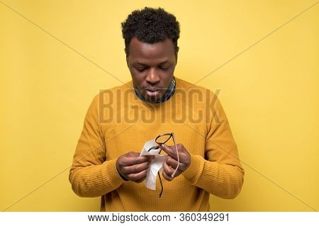 Young African American Man Cleaning Glasses With A Piece Of Tissue