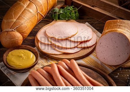 Delicious Deli Meats And Wiener Sausages On Wooden Cutting Board