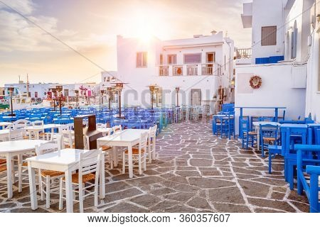 Picturesque narrow street with traditional whitewashed houses with cafe tables of Naousa town in famous tourist attraction Paros island, Greece on sunrise