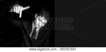 Portrait Shot Of An Arrogant Businessman Posing On A Black Colored Background In A Blue Suit With On
