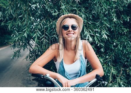 Pretty Teenage Hipster Girl With Toothy Smile In Straw Hat And Sunglasses Outdoor Over Green Leaves