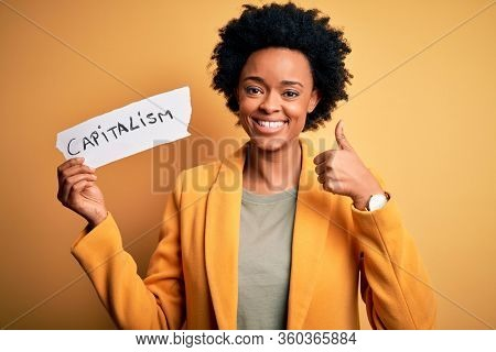 African American afro businesswoman with curly hair holding paper with capitalism message happy with big smile doing ok sign, thumb up with fingers, excellent sign