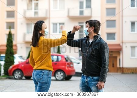 Friends Greetings With Elbows Outdoors. Woman And Man Wearing Face Mask Outdoors. Friends Shaking El