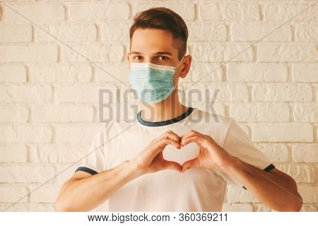 Happy Doctor In Protective Mask On Face Gesturing Heart Symbol By Hands. Young Man In Medical Face M