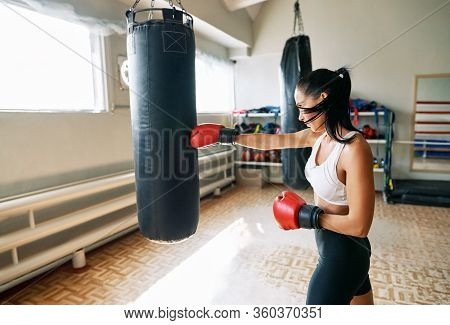 Female Boxer Hitting A Huge Punching Bag At Fitness Gym. Woman Practicing Her Punches At A Boxing St