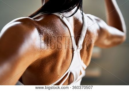 Close Up Of Woman Back With Flexing Her Muscles In Sweat On Skin After Workout. Female Bodybuilder W