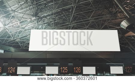 A Long Horizontal Empty Advertising Billboard Mockup Above Multiple Numbered Check-in Kiosks In A Mo