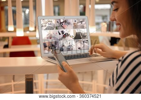 Woman Monitoring Modern Cctv Cameras On Laptop Indoors, Closeup. Home Security System