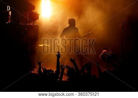 Silhouette Of The Guitarist On Stage Over The Fans.