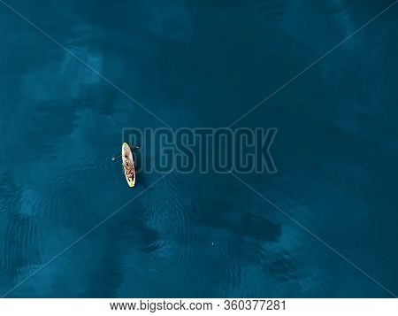 Aerial Drone View Of Family Having Fun Swimming On Sup Stand Up Paddle Inflatable Surf Board. Mother