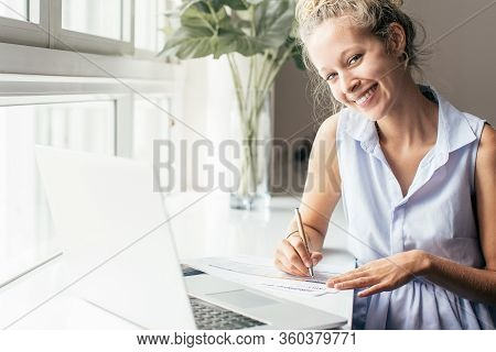 Closeup Portrait Of Smiling Young Beautiful Fair-haired Woman Looking At Camera And Working With Doc