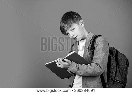 Final Exam. Little Child Take Exam Brown Background. Small Boy Write In Bluebook. Written Exam. Exam